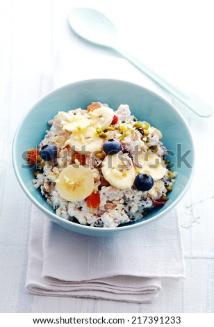 High angle view of a serving of homemade muesli topped with dried fruit, berries, sliced banana and nuts in a blue bowl on a napkin ready for a healthy tasty breakfast - stock photo