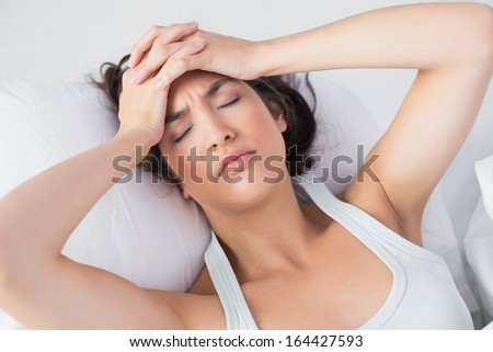 High angle view of a sleepy young woman suffering from headache with eyes closed in bed at home - stock photo