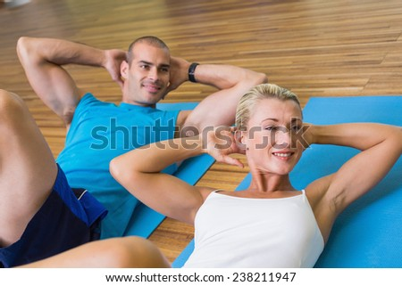 High angle view of a sporty young couple doing abdominal crunches at fitness studio - stock photo