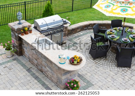 High angle view of a stylish outdoor kitchen, gas barbecue and dining table set for entertaining guests with formal place settings and flowers on a paved patio - stock photo