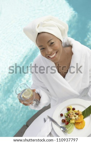 High angle view of a woman having healthy food by swimming pool - stock photo