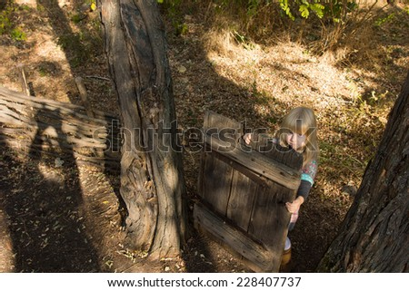 High angle view of a young blond girl playing with an old wooden gate between two trees in a garden looking up at the camera - stock photo