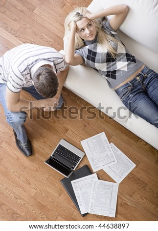 High angle view of a young couple frustrated while doing paperwork. Vertical shot. - stock photo