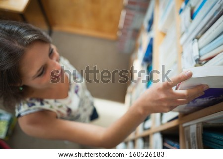 High angle view of a young female student selecting book in the library - stock photo