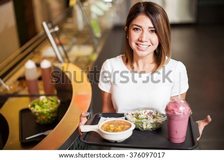 High angle view of a young woman carrying a tray with some food at a cafeteria and smiling - stock photo