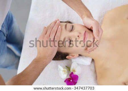 High Angle View of a Young Woman Lying on Bed and Enjoying a Head Massage in the Spa. - stock photo