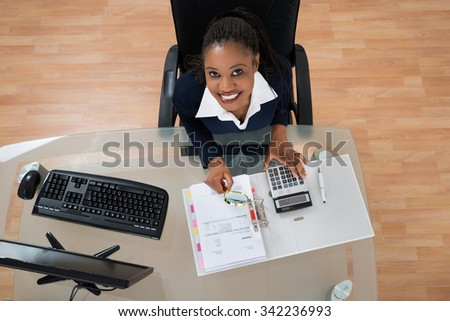 High Angle View Of African Businesswoman Looking At Invoice Through Magnifying Glass - stock photo