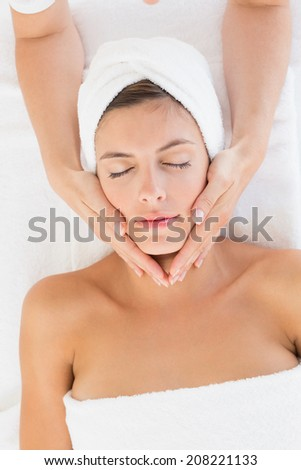 High angle view of an attractive young woman receiving facial massage at spa center - stock photo