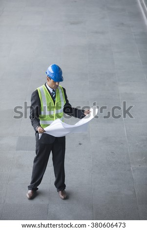 High angle view of an male Indian industrial engineer at work holding technical drawing plans. - stock photo