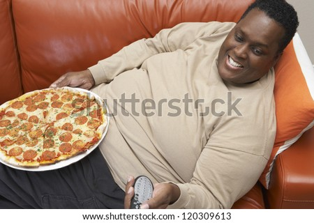 High angle view of an obese African American man watching television with pizza ob lap - stock photo