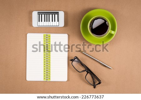 High angle view of black digital tablet with isolated white screen. Green notebook or blank paper notes, glasses, pen and green coffee mug on wooden surface.  - stock photo