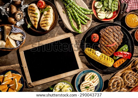 High Angle View of Blank Chalkboard Amongst Grilled Meal of Steak, Chicken and Vegetables Spread Out on Rustic Wooden Table at Barbeque Party - stock photo
