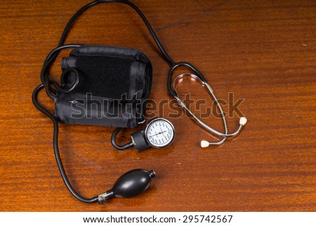 High Angle View of Blood Pressure Cuff and Stethoscope Medical Supplies on Wooden Table with Copy Space - stock photo
