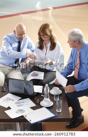 High angle view of business people analyzing data at digital tablet. Teamwork at office.  - stock photo