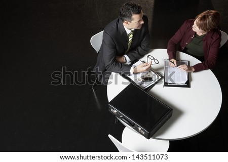 High angle view of business people discussing paperwork at desk - stock photo