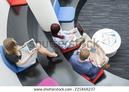 High angle view of business people sitting in office lobby - stock photo