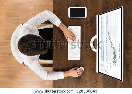 High Angle View Of Businessman Analyzing Graph On Desktop Computer - stock photo