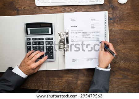 High Angle View Of Businessman's Hand Calculating Invoice Using Calculator - stock photo