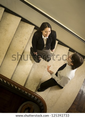 High angle view of businessman talking to businesswoman on stairway - stock photo