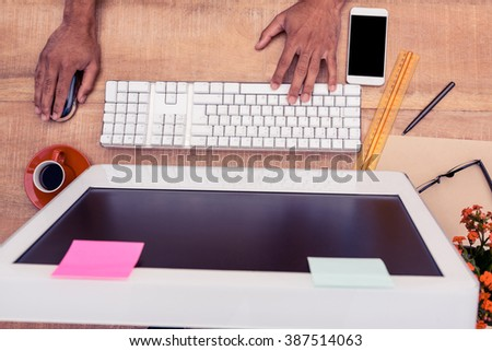 High angle view of businessman typing keyboard while working at desk in office - stock photo