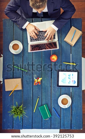 High angle view of businessman using laptop at desk in office - stock photo