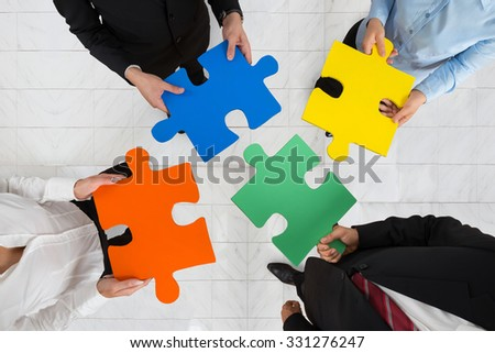 High Angle View Of Businesspeople Team Holding Colorful Puzzle Pieces In Hands - stock photo