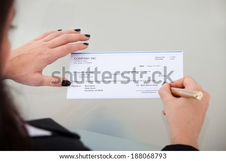 High angle view of businesswoman signing cheque at desk in office - stock photo