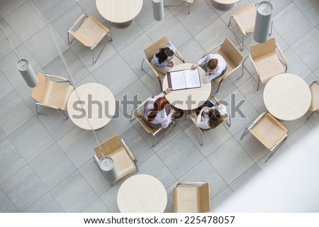 High angle view of businesswomen doing paperwork in office canteen - stock photo