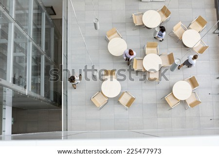High angle view of businesswomen walking at office canteen - stock photo
