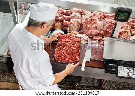 High angle view of butcher holding minced meat tray at display cabinet in butchery - stock photo