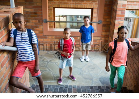 High angle view of classmates standing at school corridor - stock photo