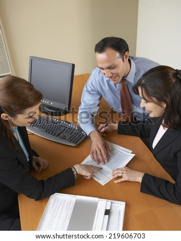 High angle view of couple examining a document - stock photo