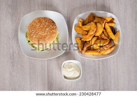 High angle view of delicious burger and fried potatoes served in plates on floor - stock photo