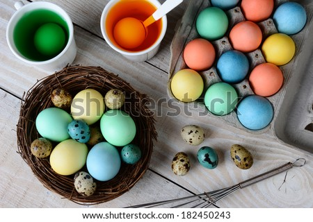 High angle view of Easter Egg dying. Dyed eggs in a nest with eggs in dye solution. Horizontal format on a rustic farmhouse style kitchen table. - stock photo