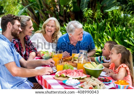 High angle view of family having food at table in yard - stock photo