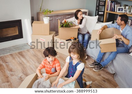 High angle view of family unpacking cardboard boxes in living room - stock photo