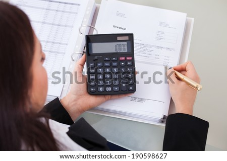 High angle view of female accountant calculating tax at desk in office - stock photo