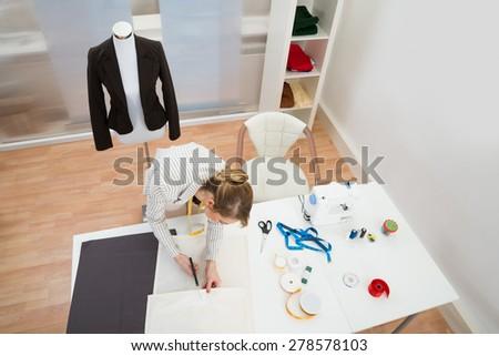 High Angle View Of Female Fashion Designer Cutting Fabric In Studio - stock photo