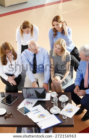 High angle view of financial business people sitting at meeting. Businesswomen and businessmen sitting at desk in front of computer and consulting from financial investment. Teamwork at office.  - stock photo
