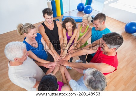 High angle view of fit people stacking hands at health club - stock photo