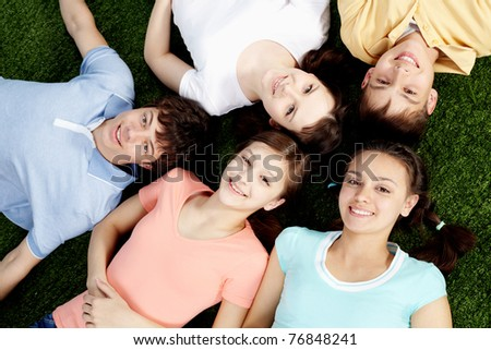 High angle view of five happy teens lying on grass - stock photo
