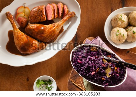 High angle view of german tradition food. Chicken drumsticks, red cabbage and traditional dumplings in overhead view on a brown wooden background - stock photo