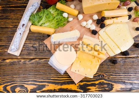 High Angle View of Gourmet Cheese Board Featuring Variety of Cheeses, Cured Meats and Fresh Fruit Served on Rustic Wooden Table with Wood Grain and Copy Space - stock photo