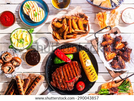 High Angle View of Grilled Meal - Appetizing Barbequed Meats and Vegetables Arranged on White Wooden Picnic Table - stock photo
