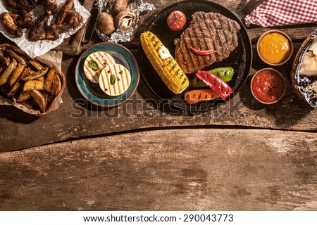 High Angle View of Grilled Meal of Steak, Chicken and Vegetables Spread Out on Rustic Wooden Table at Barbeque Party - stock photo