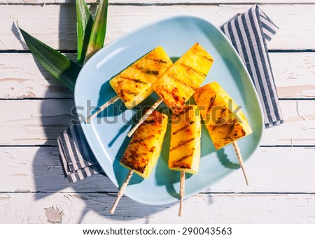 High Angle View of Grilled Skewers of Fresh Pineapple Wedges on Blue Plate on White Wooden Table with Striped Napkin - stock photo