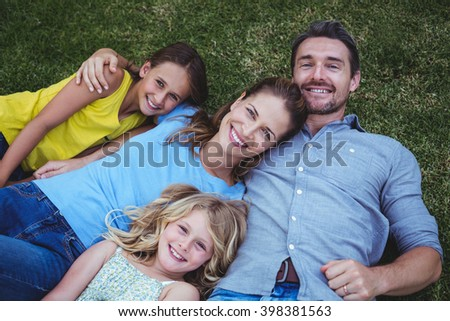 High angle view of happy family lying on field in back yard - stock photo