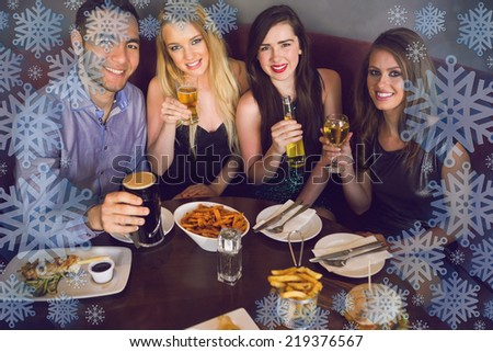 High angle view of happy friends having dinner together against snowflake frame - stock photo