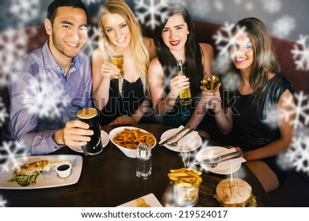 High angle view of happy friends having dinner together against snowflakes - stock photo