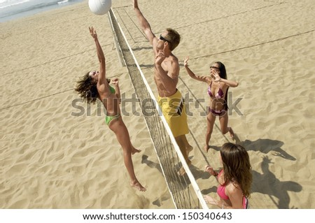 High angle view of happy multiethnic friends playing volleyball on beach - stock photo